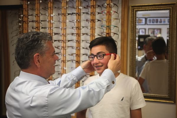 Joseph Carbone giving glasses to a kid